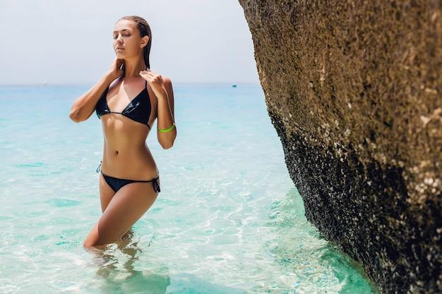 Mulher jovem e sexy esguia, corpo lindo e perfeito, pele bronzeada, maiô de biquíni preto, banho de sol no oceano de águas azuis cristalinas, férias de verão na ásia, sensual, quente, viagem na tailândia, praia tropical