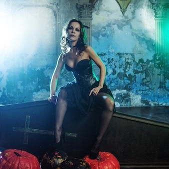 Mulher jovem e sexy, imagem de bruxas em um cemitério, sentado no caixão de tampa.