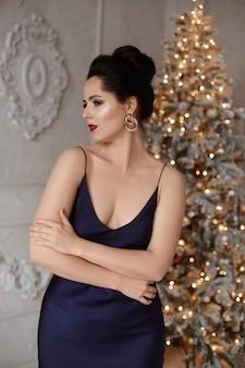 Mulher jovem e sexy linda com maquiagem perfeita, usando um vestido de noite azul, posando com o natal festivo.