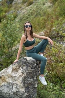 Mulher jovem e sexy posando perto de uma pedra grande e grama alta verde, aventura de verão perfeita