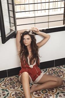 Mulher jovem e sexy usando macacão sentada no chão de ladrilhos