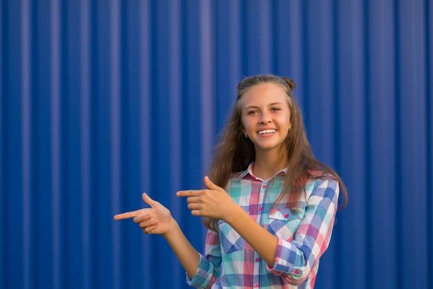 Mulher jovem e simpática apontando para o lado com as duas mãos enquanto fica em frente a uma parede ondulada azul colorida