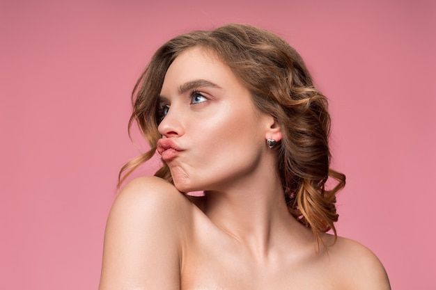 Mulher jovem e simpática com cabelo sedoso longo ondulado, maquiagem natural com a mão perto do queixo isolado na parede rosa. modelo com maquiagem natural.