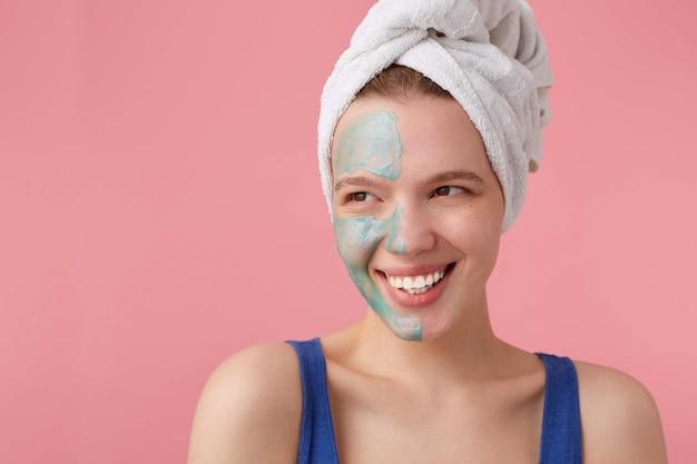 Mulher jovem e simpática com meia máscara facial, com uma toalha na cabeça depois do banho, sorrindo e olhando para longe, em pé.