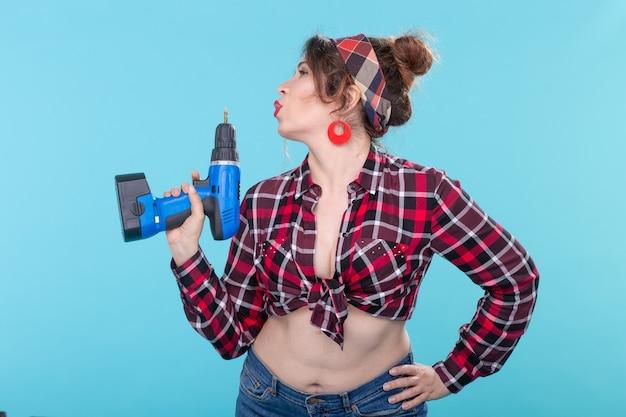 Mulher jovem e simpática com roupas retrô, segurando um nas mãos, representando uma pistola em uma parede azul