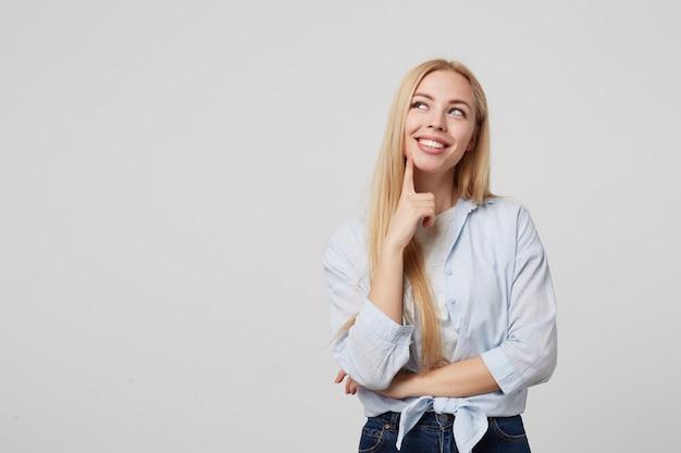 Mulher jovem e sonhadora e feliz com o dedo indicador no queixo e olhando para o lado, pensativa, vestindo jeans e camisa azul, em pé