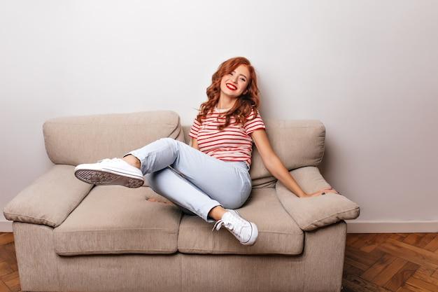 Mulher jovem e sonhadora em sapatos desportivos expressando felicidade durante a sessão de fotos em casa. garota gengibre em jeans casuais, sentada no sofá.