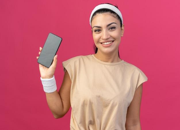 Mulher jovem e sorridente, caucasiana, esportiva, usando fita para a cabeça e pulseiras, olhando para a frente, mostrando o celular para a câmera isolada na parede rosa