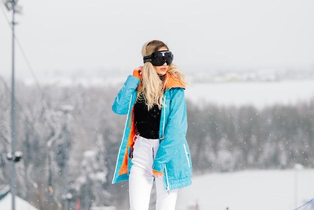 Mulher jovem e sorridente desportiva no inverno com snowboard