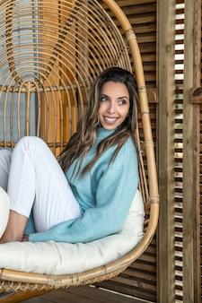 Mulher jovem e sorridente encantadora com roupas brancas e azuis, sentada em uma confortável cadeira de vime de vime enquanto relaxa no terraço da casa