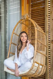 Mulher jovem e sorridente encantadora com roupas brancas, sentada em uma confortável cadeira de vime de vime enquanto relaxa no terraço da casa