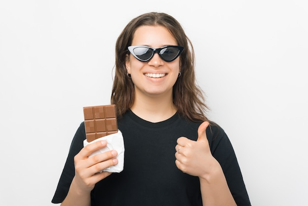 Mulher jovem e sorridente está segurando uma barra de chocolate e o polegar.