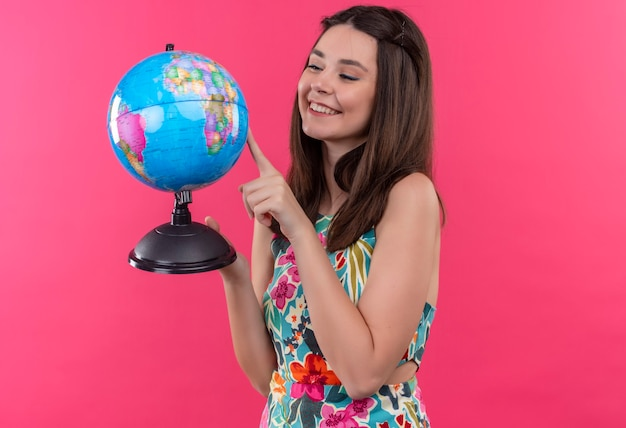 Mulher jovem e sorridente feliz segurando um globo terrestre e apontando com o dedo para ele na parede rosa isolada