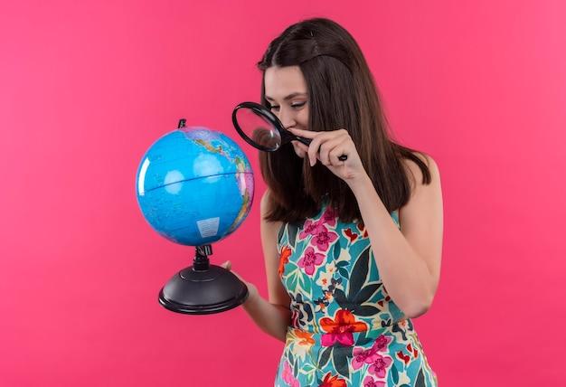 Mulher jovem e sorridente feliz segurando um globo terrestre e uma lupa na parede rosa isolada