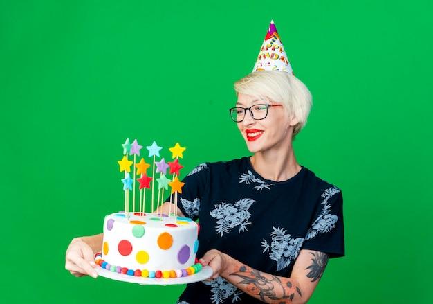 Mulher jovem e sorridente, festa loira usando óculos e boné de aniversário segurando e olhando para um bolo de aniversário isolado na parede verde com espaço de cópia