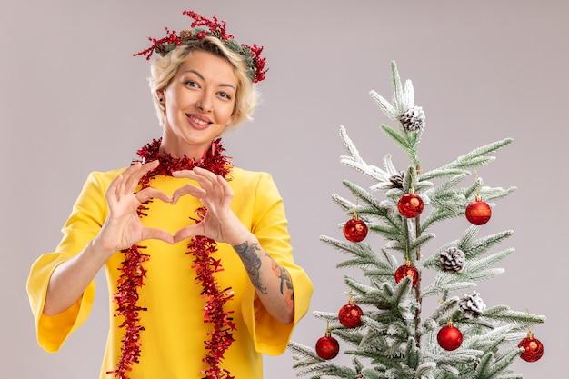 Mulher jovem e sorridente loira com coroa de flores de natal e guirlanda de ouropel em volta do pescoço, em pé perto da árvore de natal decorada, olhando para a câmera, fazendo um sinal de coração isolado no fundo branco