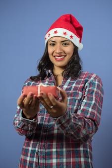 Mulher jovem e sorridente olhando para a frente segurando um pequeno presente de natal