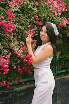 Mulher jovem e sorridente perto do espaço da cópia do arbusto de rosas vermelhas florescendo