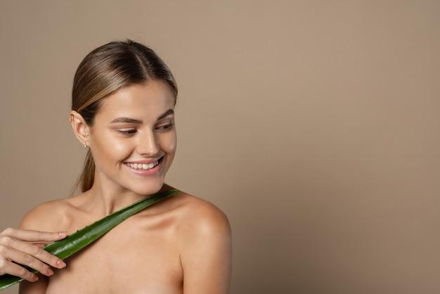 Mulher jovem e sorridente segurando uma folha de aloe vera nas mãos