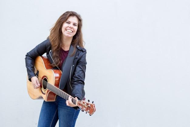 Mulher jovem e sorridente tocando guitarra