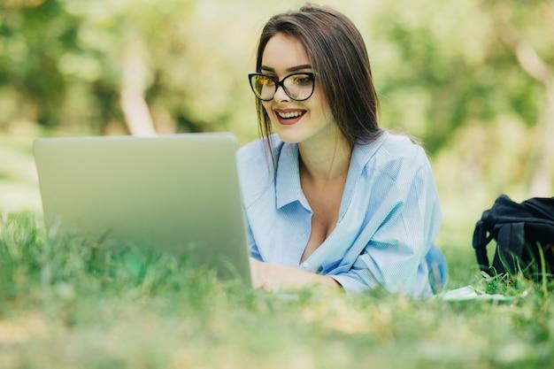 Mulher jovem e sorridente usando laptop no parque da cidade em um dia ensolarado
