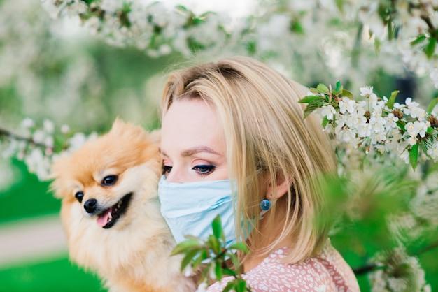 Mulher jovem e spitz vermelho com uma máscara médica no rosto na natureza em um dia de primavera. coronavírus