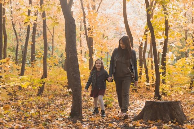 Mulher jovem e sua filha caminhando pelo parque de outono mãe solteira e o conceito de maternidade