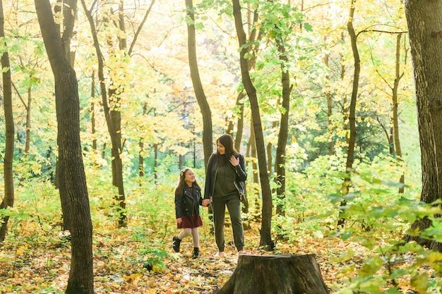 Mulher jovem e sua filha caminhando pelo parque mãe solteira e conceito de maternidade