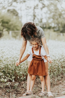 Mulher jovem e sua filha com cabelo encaracolado