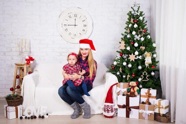 Mulher jovem e sua filha com caixas de presente de natal e árvore de natal na sala de estar