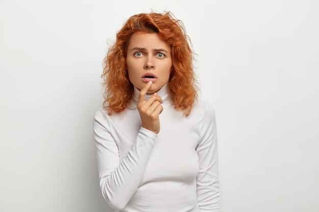 Mulher jovem e surpresa que olha atentamente com a boca aberta, reage a algo surpreendente, tem cabelos ruivos, olhos verdes, usa gola olímpica casual, isolada na parede branca