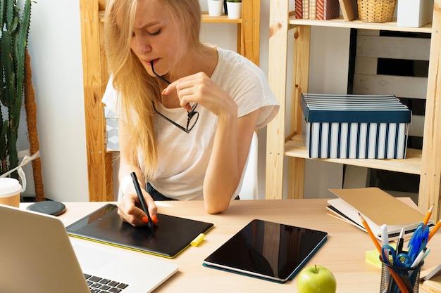 Mulher jovem e tablet trabalhando no escritório em casa. fique seguro e trabalhando em casa.