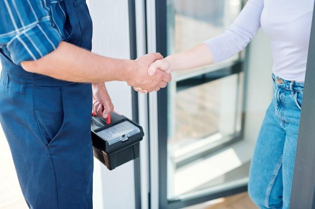 Mulher jovem e técnico ou encanador com caixa de ferramentas se despedindo enquanto apertam as mãos após o trabalho de reparo