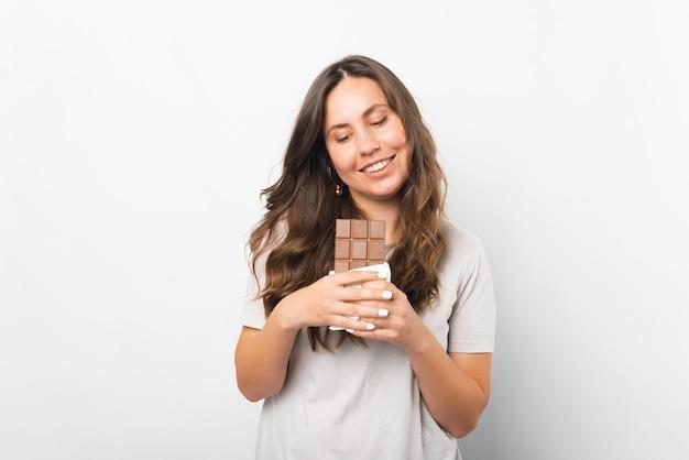Mulher jovem é tentada a morder um pedaço de chocolate que está segurando.