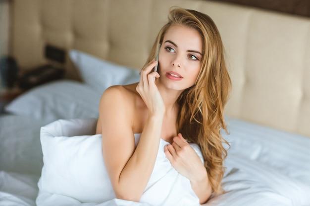 Mulher jovem e tranquila e sensual falando no celular na cama