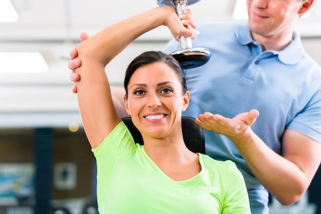 Mulher jovem e treinadora fazendo exercícios na academia com halteres