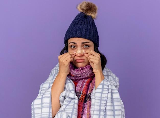 Mulher jovem e triste com chapéu de inverno e lenço embrulhado em xadrez, olhando para frente, colocando gesso no nariz isolado na parede roxa