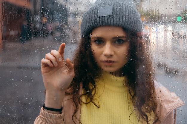 Mulher jovem e triste e encaracolada fica sozinha no vidro com gotas em dia chuvoso