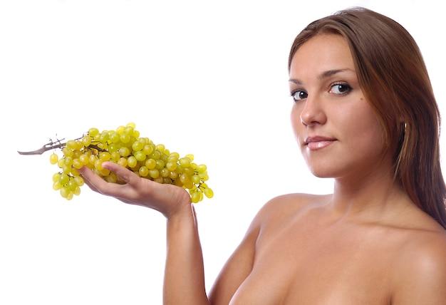 Mulher jovem e um cacho de uvas verdes maduras