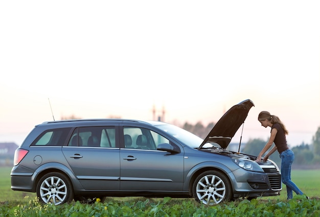 Mulher jovem e um carro com capô estourado. transporte, problemas de veículos e conceito de avarias.