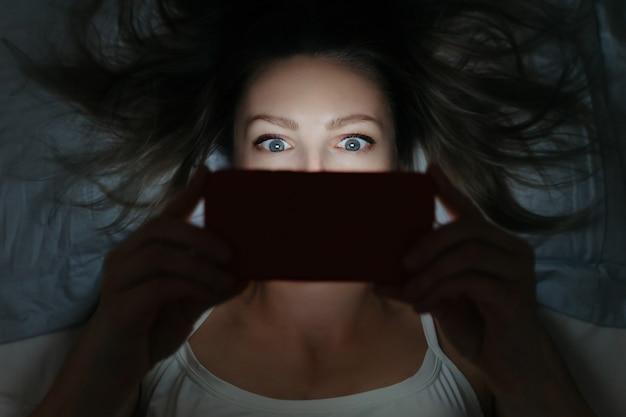 Mulher jovem e viciante olhando para o smartphone tarde da noite na cama