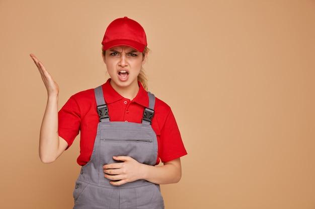 Mulher jovem e zangada da construção civil vestindo uniforme e boné, mantendo a mão na barriga, mostrando a mão vazia