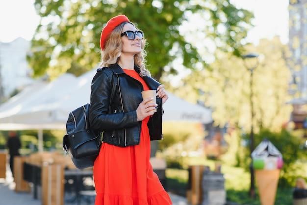Mulher jovem elegante alegre na rua bebendo café da manhã na luz do sol.