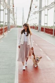 Mulher jovem elegante andando com cachorro corgi ao ar livre.