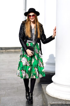 Mulher jovem elegante andando na rua com jaqueta de couro e saia floral