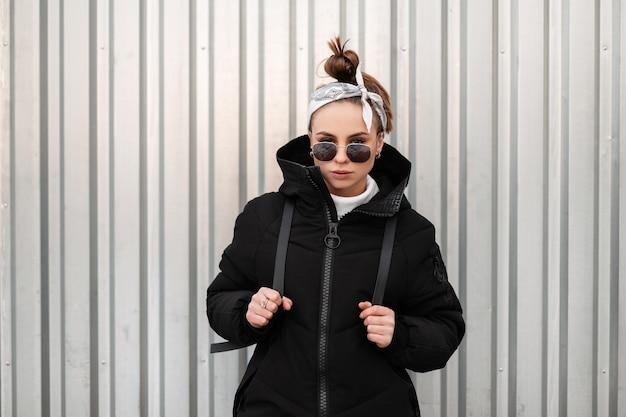 Mulher jovem elegante bonita hippie com um penteado elegante com uma bandana em óculos de sol pretos em um casaco preto longo com uma mochila nos ombros posa perto de uma parede de metal. garota moderna e elegante