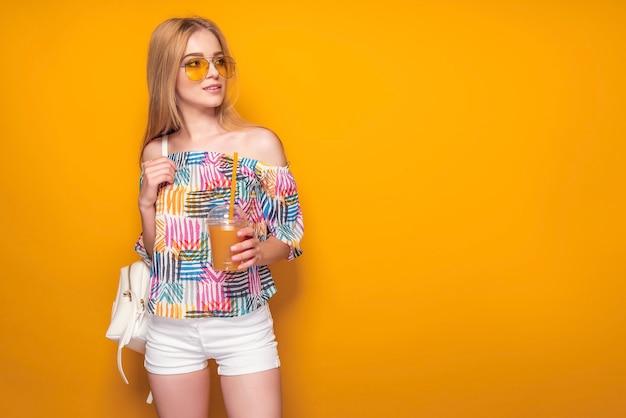 Mulher jovem elegante com bebida em uma parede amarela