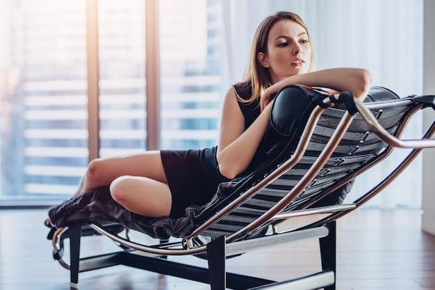 Mulher jovem elegante com cabelo loiro em um vestido preto deitado na poltrona, apoiando a cabeça dela com a mão, olhando pela janela panorâmica, apreciando a paisagem urbana.
