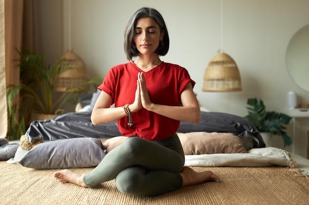 Mulher jovem elegante com cabelos grisalhos sentada em gomukhasana ou postura de vaca enquanto pratica hatha ioga no quarto após acordar, mantendo os olhos fechados e pressionando as mãos juntas em namaste