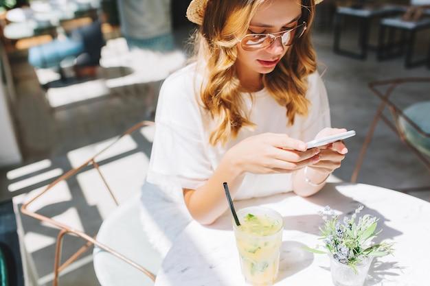 Mulher jovem elegante com camisa branca e óculos da moda enviando mensagens de texto durante o descanso no café sozinha